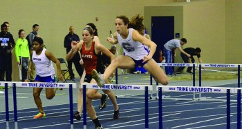 Mollie Nebel, a senior, leaps over a hurdle during the track invitational at Trine University