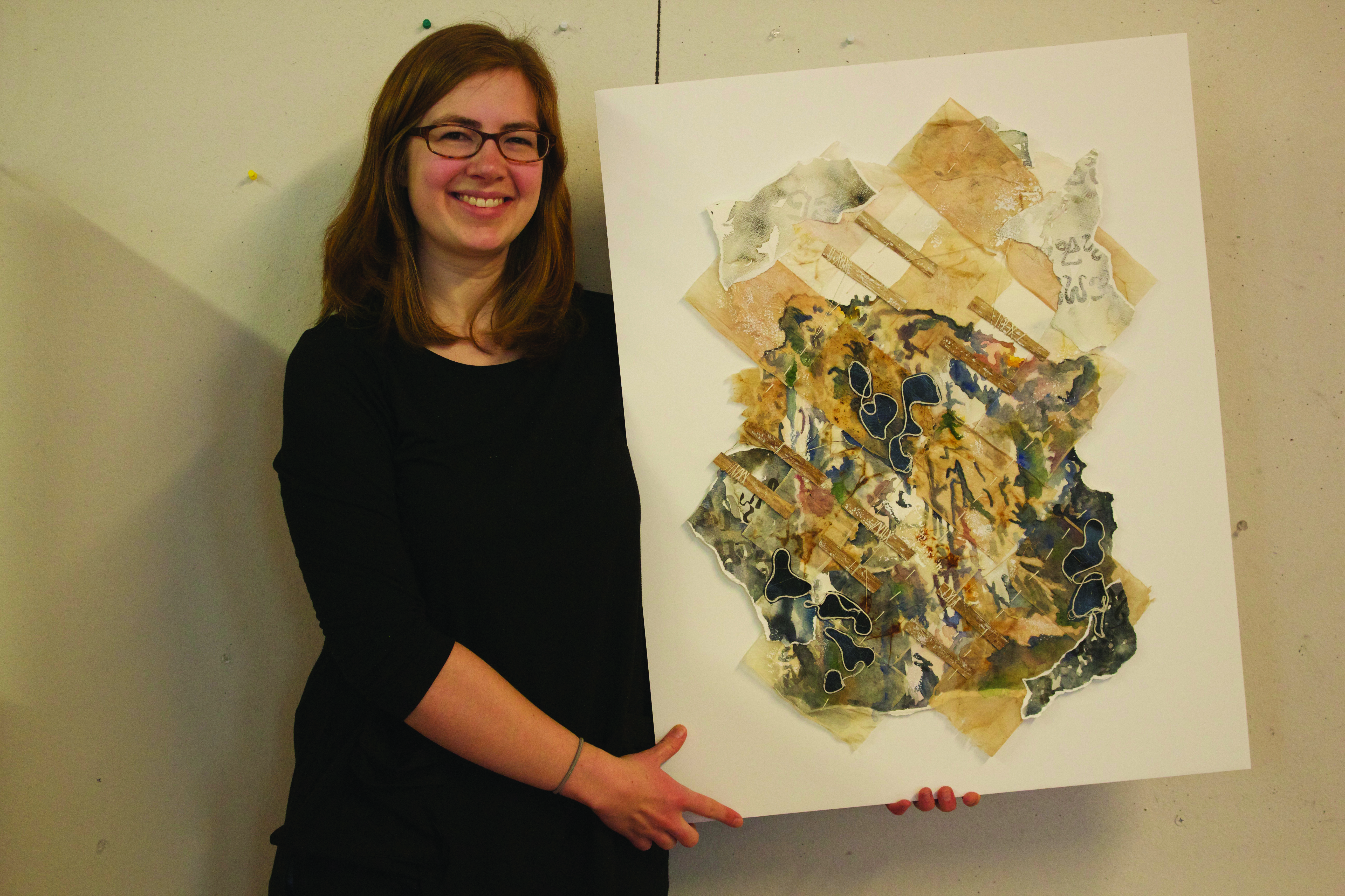 Kate Yoder holds one of her paintings and smiles for the camera