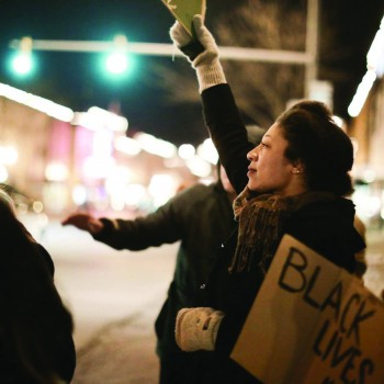 Dominique Chew, a senior, holds a sign during student Ferguson protest in downtown Goshen.