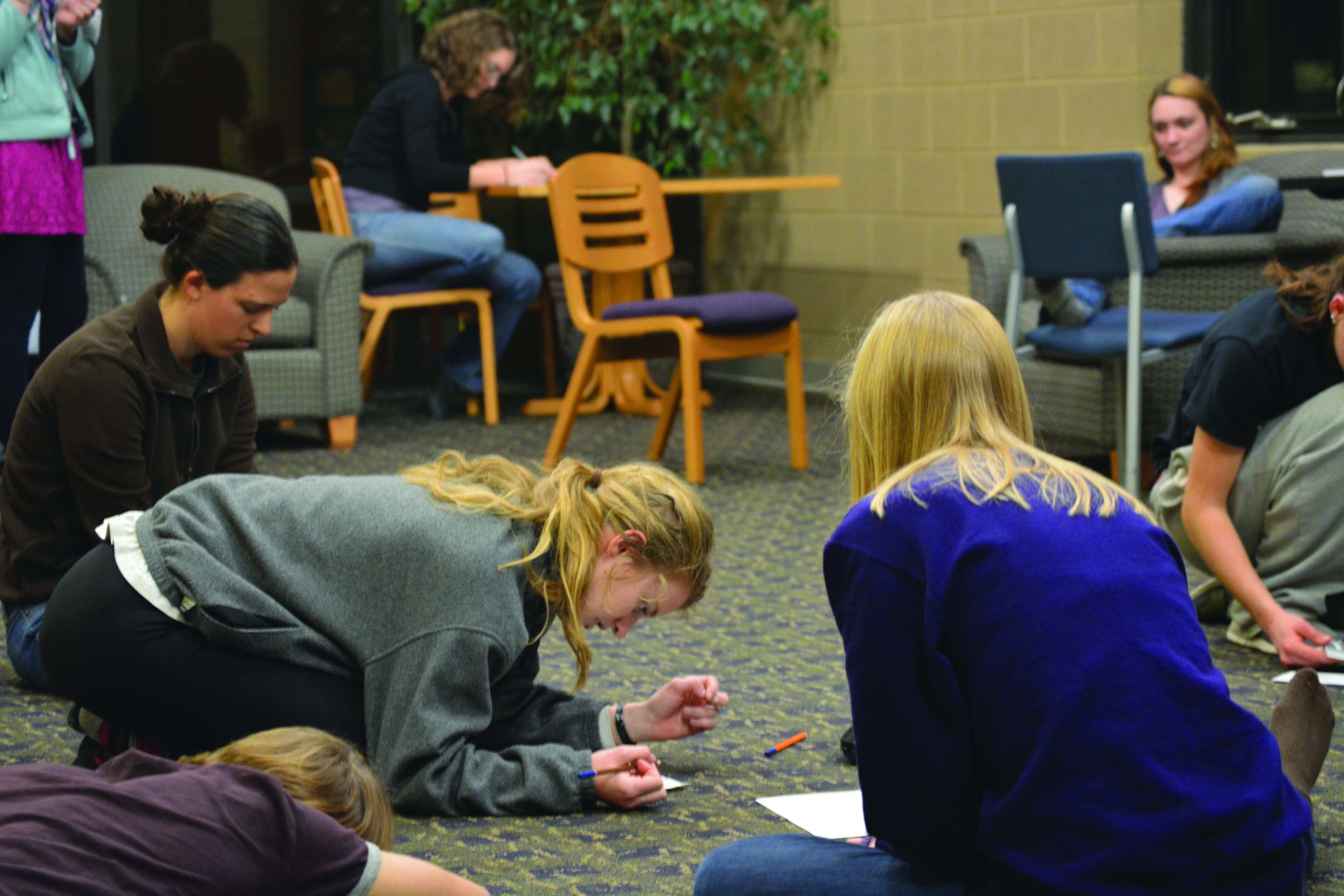 Kelly Miller and other students fill out worksheets in a dorm connector during a reflective exercise for the Conversations on Mental Health event