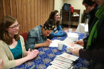 Kate Yoder, senior, Dominique Chew, senior, and Elizabeth Derstine, junior sign their books at the Pinchpenny release party.