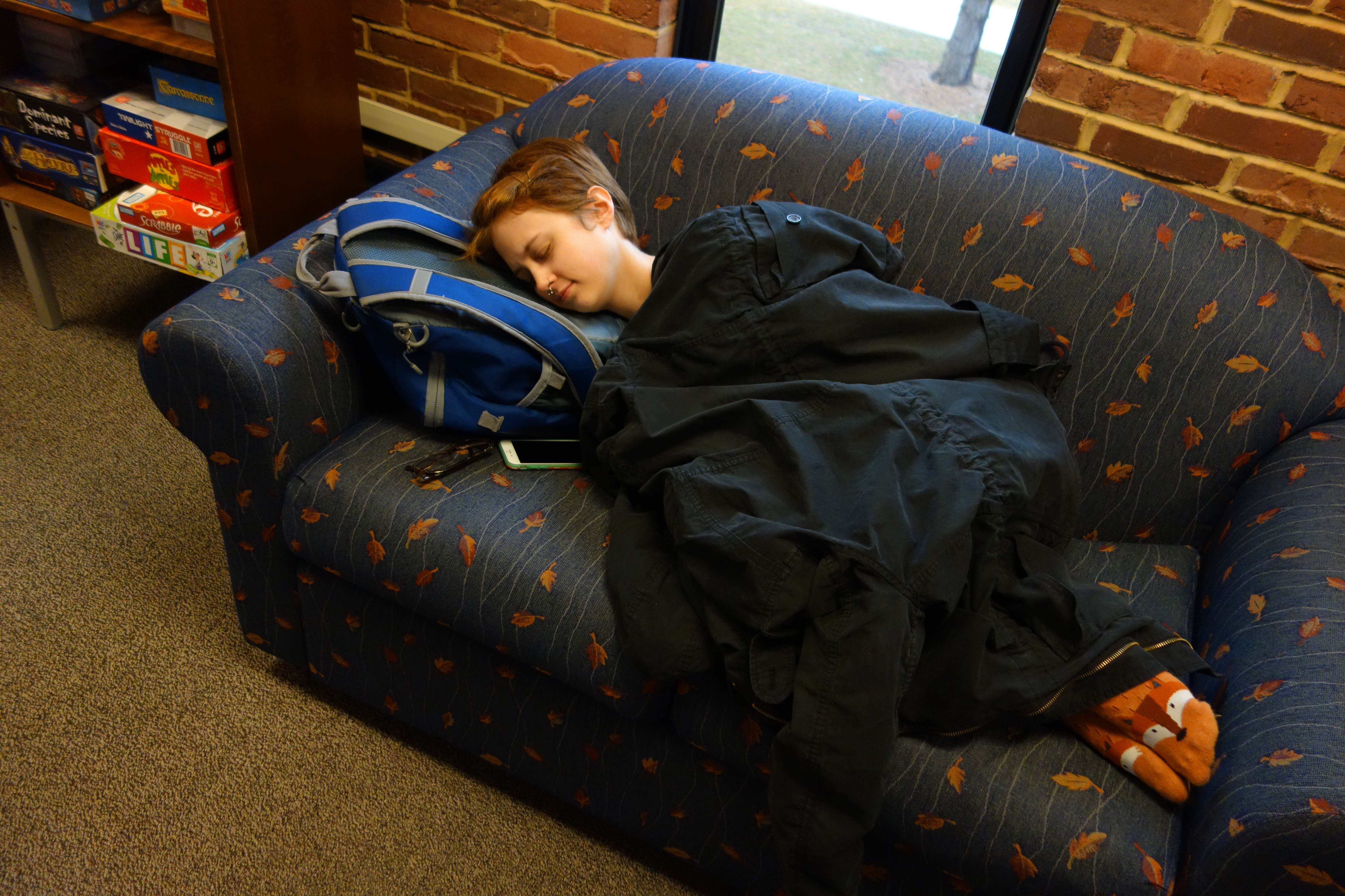 A student sleeps on a couch