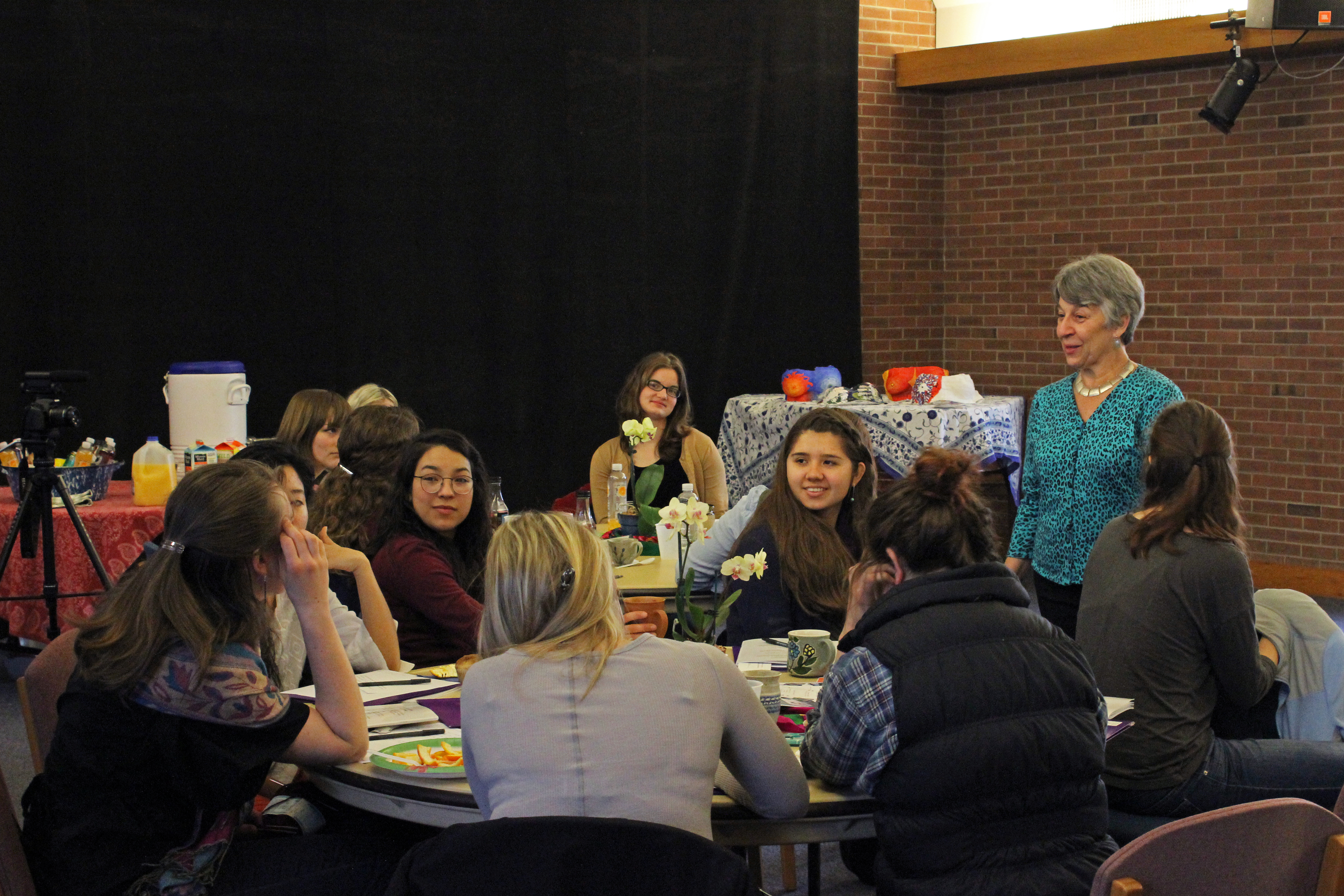 Students sit around a table in Newcomer 19 during the Sister Care event