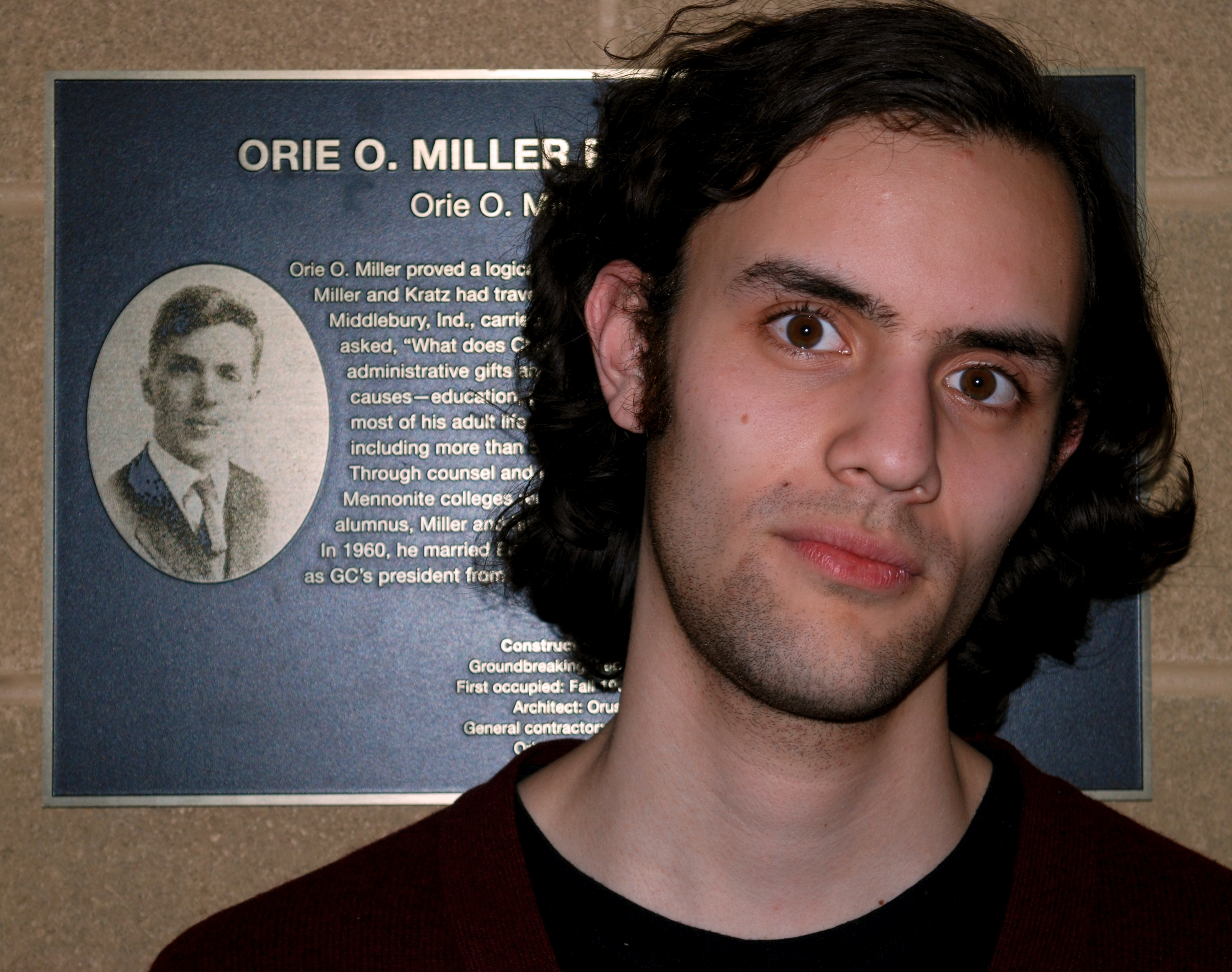 A student poses with the Orie O. Miller plaque outside Miller Residence Hall