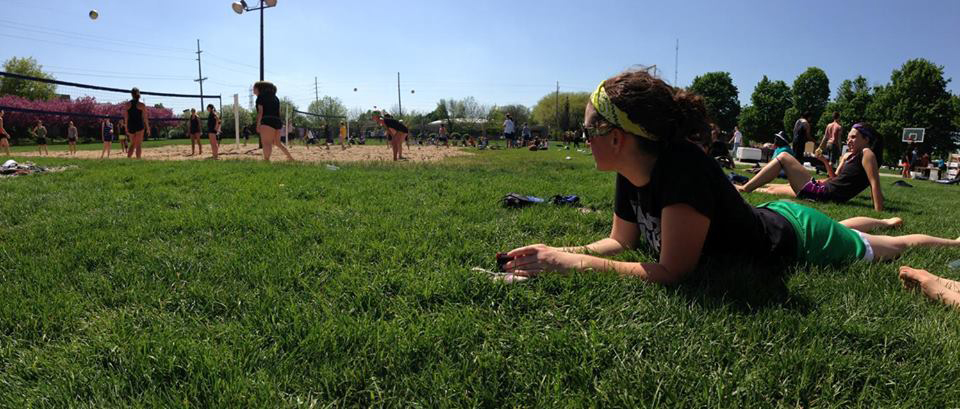 A student rests on the lawn while watching an intramural sports game