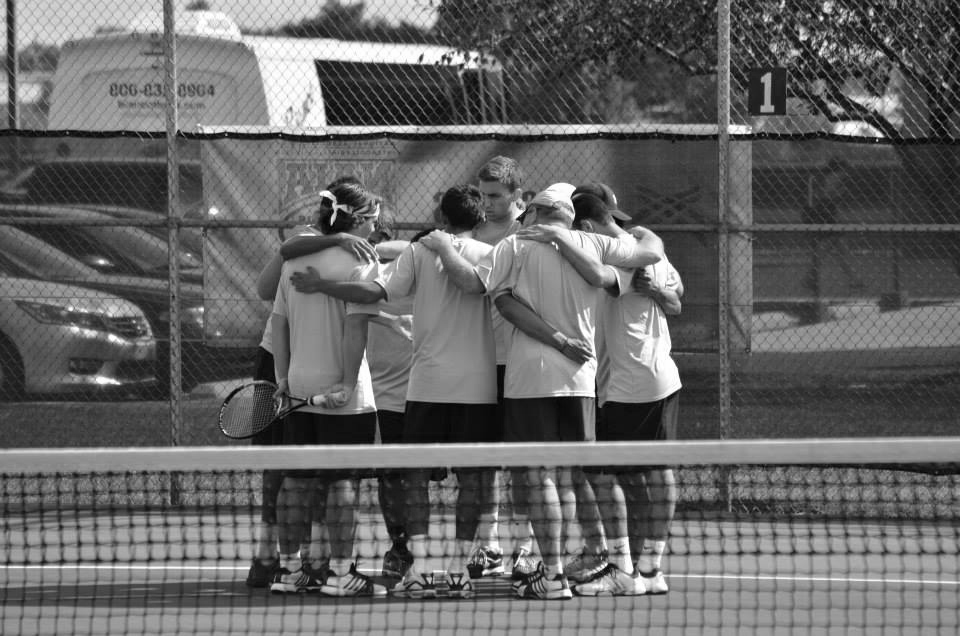 Black and white photo of the men's tennis team huddling on the court between matches