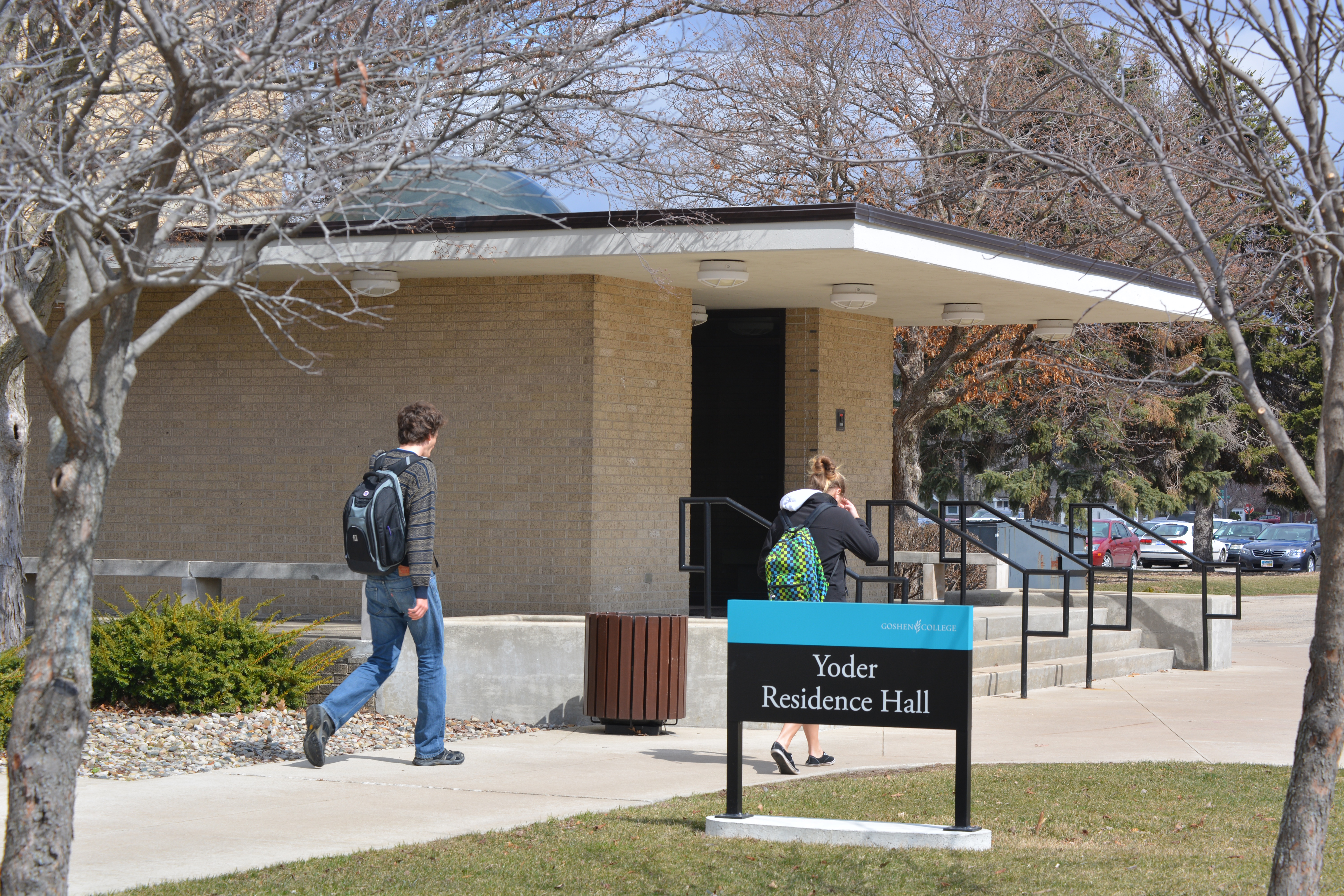 Students walk to class past Yoder Residence Hall