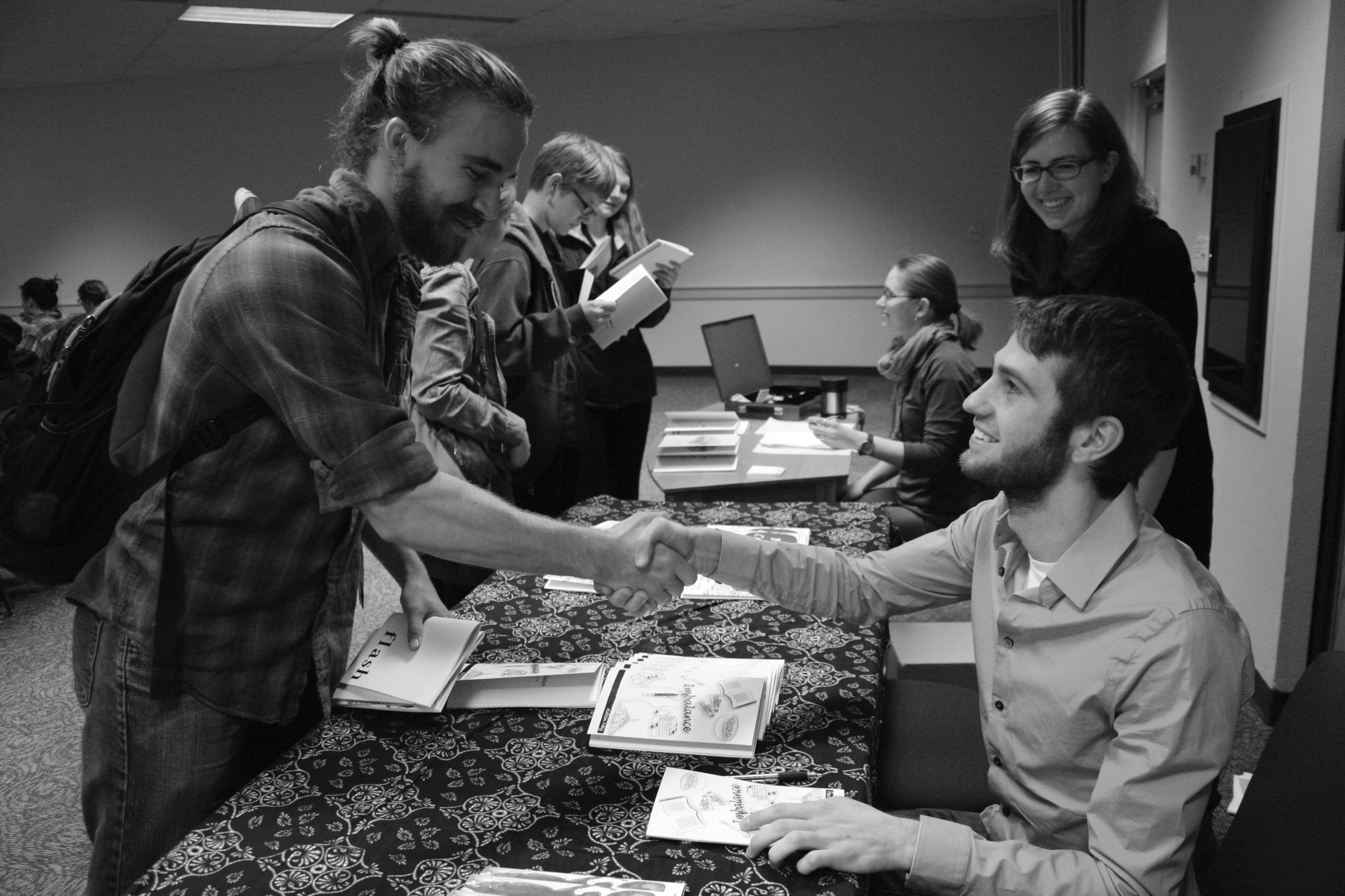 Isaiah Friesen and Kolton Nay shake hands after Nay signs his book at the Pinchpenny release party