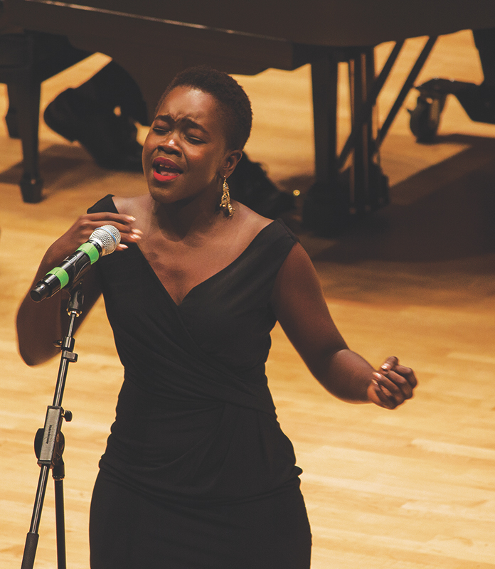 """Sophomore Achieng Agutu performs the co-written poem """"Light Another Candle, Say Another Prayer"""" with Ammon Allen-Ducot, a senior. Photo by Hannah Sauder."""