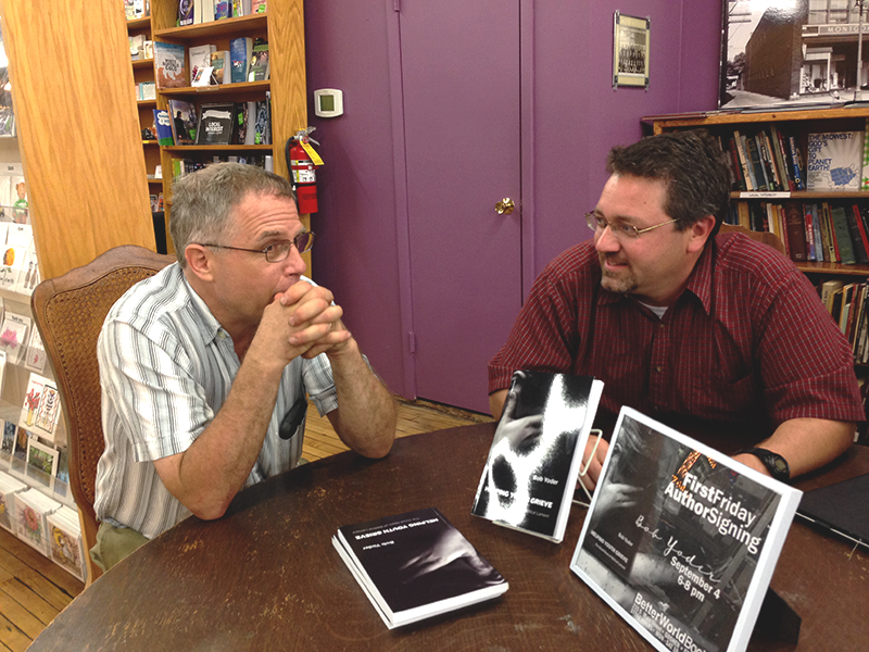 Bob Yoder discusses his new book with a community member at First Fridays last week.  Photo by Sadie Gustafson-Zook.