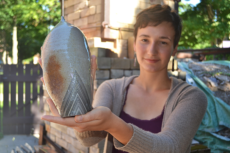 Maddie Gerig with a ceramic pot