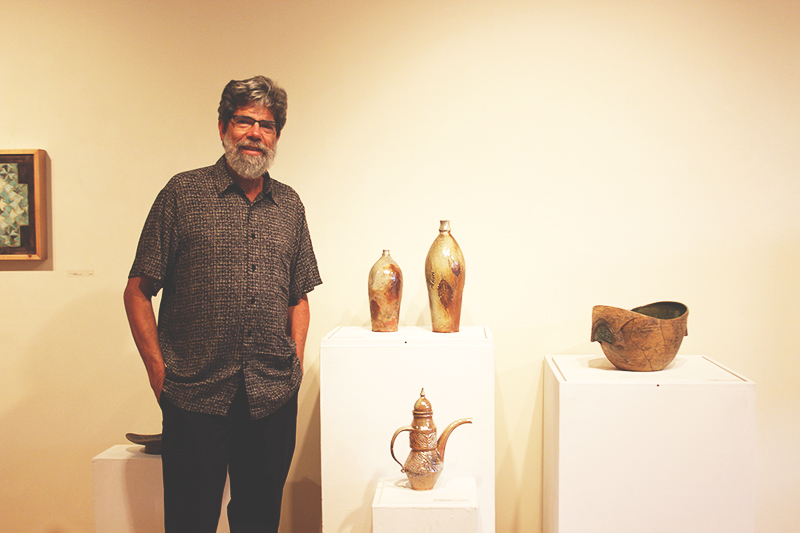 Dennis Maust poses with his ceramic pieces in the Hershberger Art Gallery