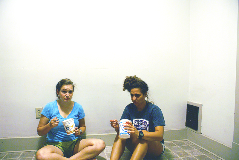 Elizabeth Franks-North and Lynelle Leinbach eat ramen on the floor of their new apartment