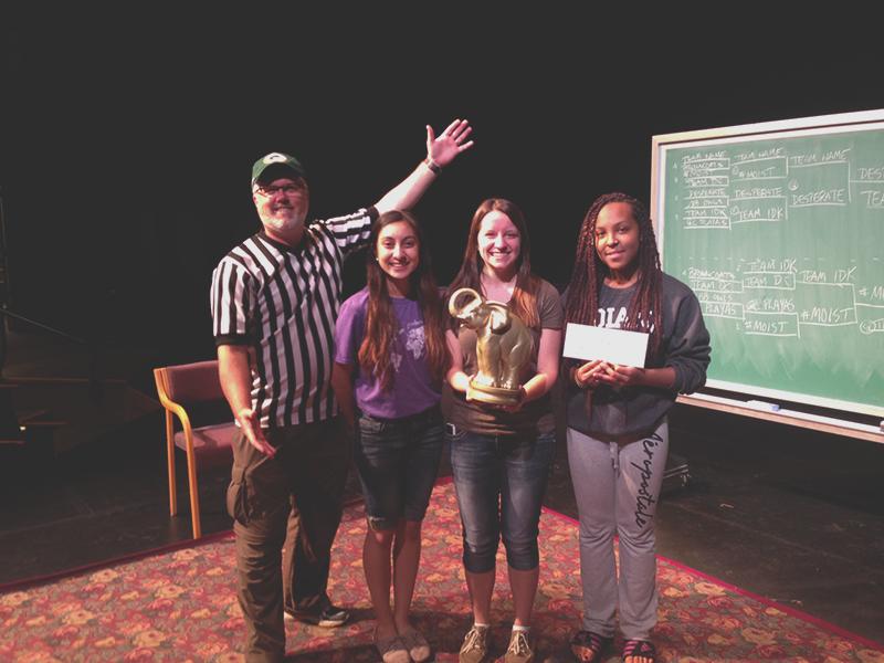 Doug Liechty-Caskey presents charades tournament winners Karina Palos, Monica Miller and A'Sean Street