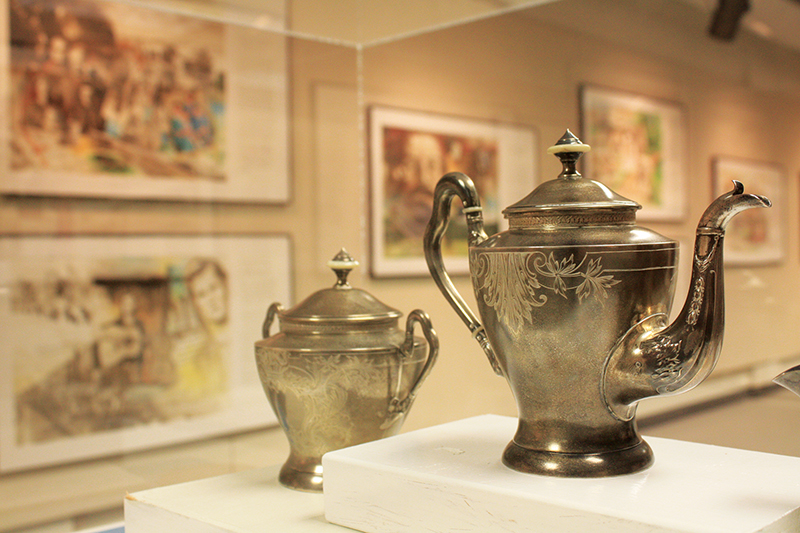 """Closeup of two pewter teapots in the """"Along the Road to Freedom: Menonite Women of Courage and Faith"""" exhibit"""