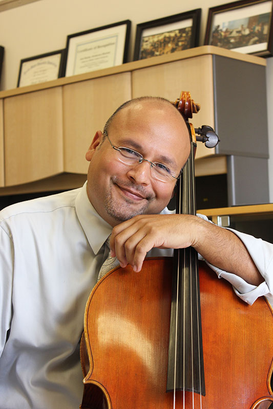 Jose Rocha poses for a picture with his cello
