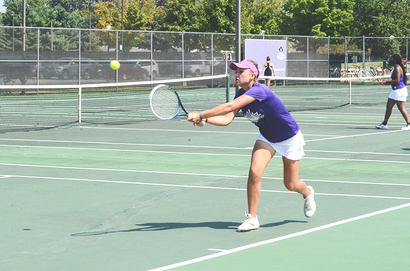 Kendra Lozano, first-year, backhands during 6th women's tennis match.