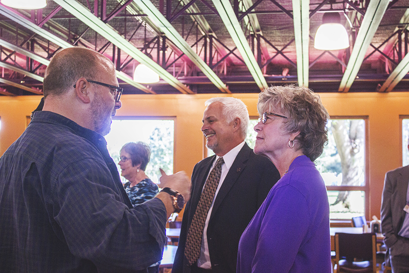 Vickie Miller celebrates her retirement with Joe Liechty and Jim Brenneman in Westlawn Dining Hall after 21 years of service.  Photo by Hannah Sauder.