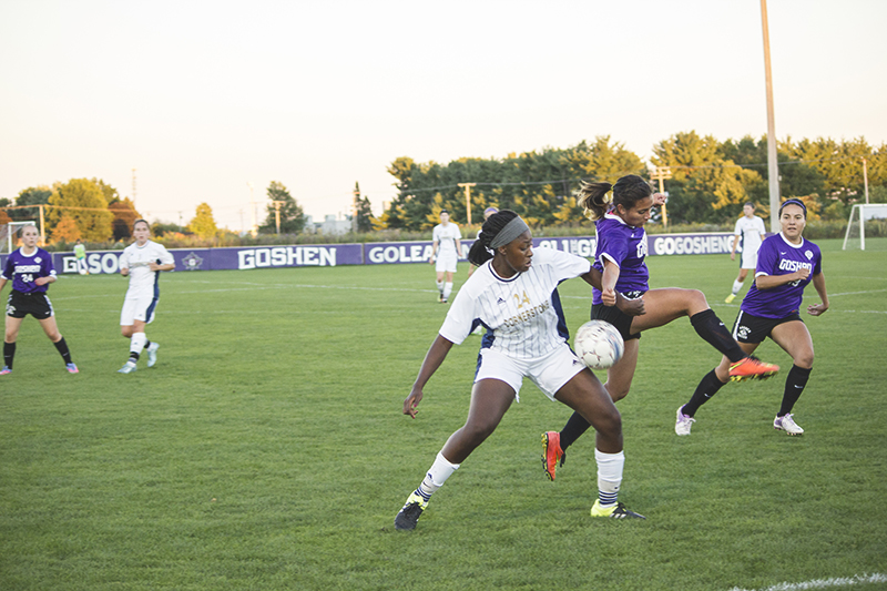A Cornerstone women's soccer player fends off a Goshen player as she dribbles the ball during a game