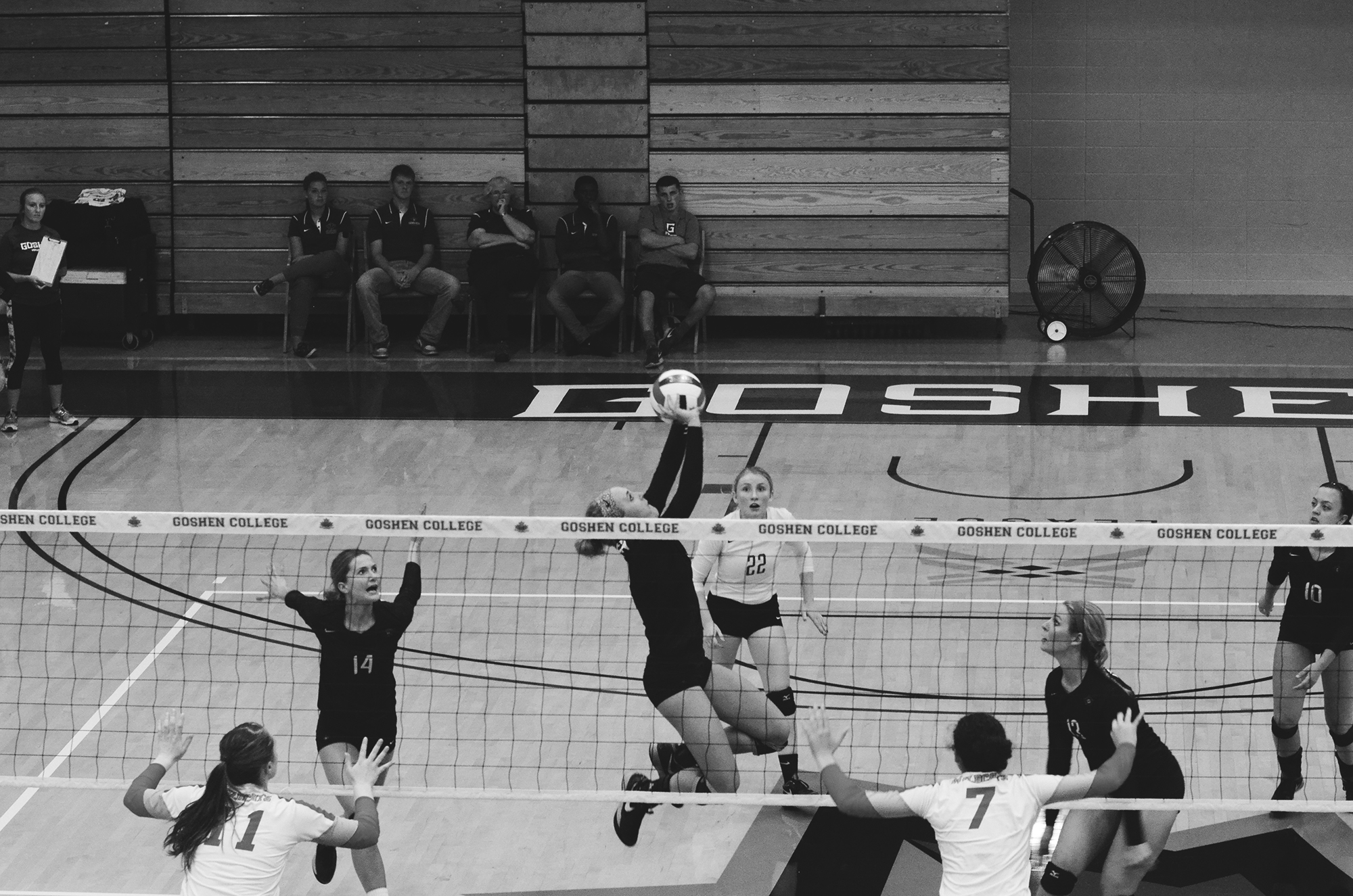 Black and white image of the Goshen women's volleyball team playing a game against St. Francis