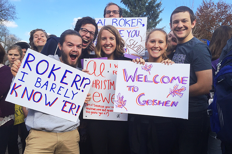 """Brianne Brenneman and other students hold up signs reading """"Welcome to Goshen"""" and """"Roker? I barely know her!"""""""