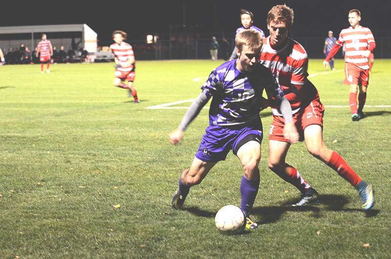 Nate Nussbaum dribbles the ball away from an opposing player during a soccer game