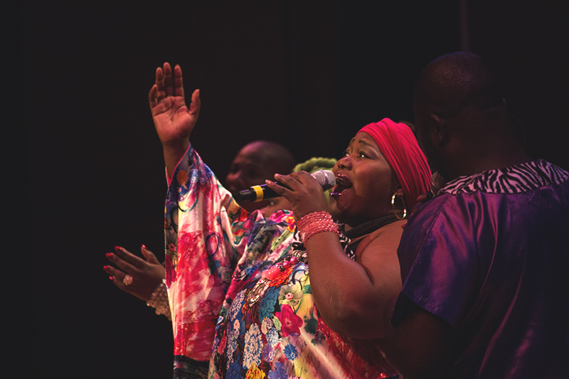 A member of the Soweto Gospel Choir sings into a microphone and raises their hand in the air