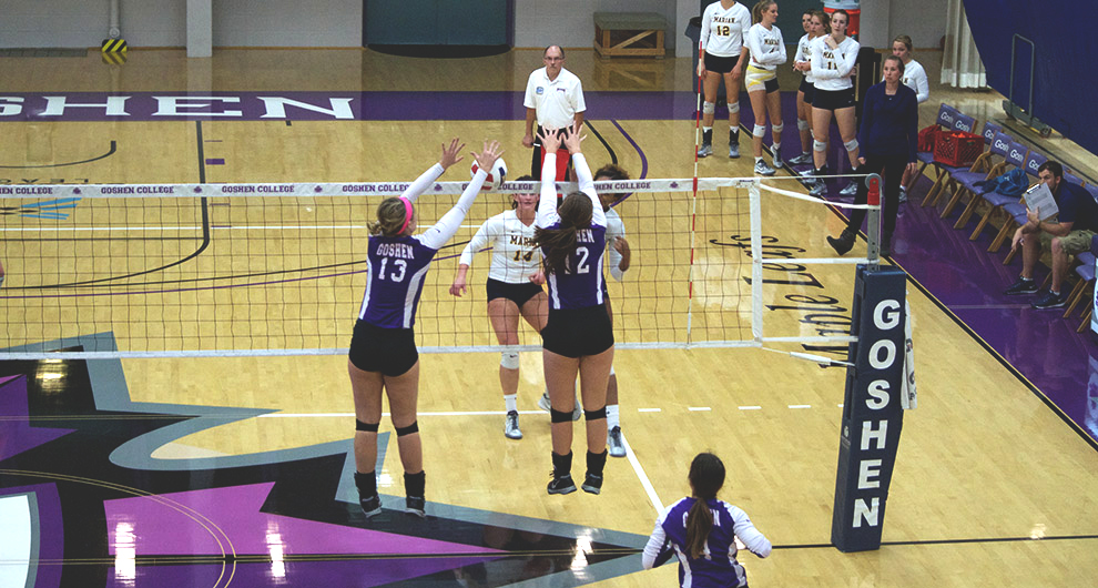 Players on the Goshen women's volleyball team jump up to block a hit from the Mount Vernon team during a game