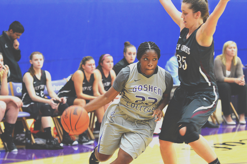 Lynnia Noel dribbles the ball around an opposing player during a basketball game