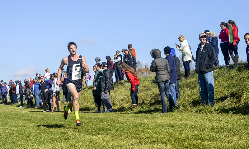Luke Graber sprints toward the finish line during a cross country race as spectators cheer him on from the sidelines