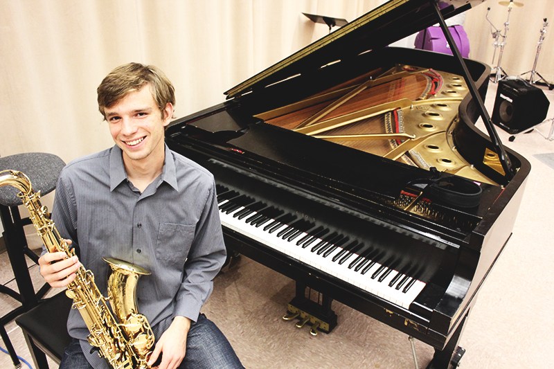 Jacob Penner sits at a grand piano and holds a saxophone