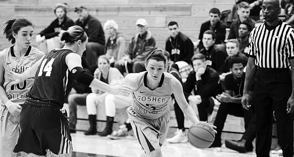Black and white image of Liz Tecca dribbling the ball past an opposing player during a basketball game