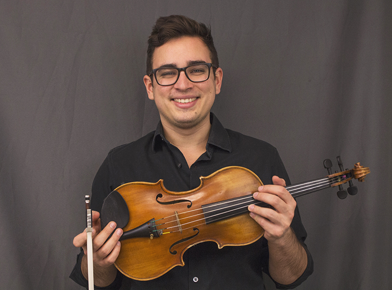 Jorge Abreu Toyens smiles for a picture with his violin