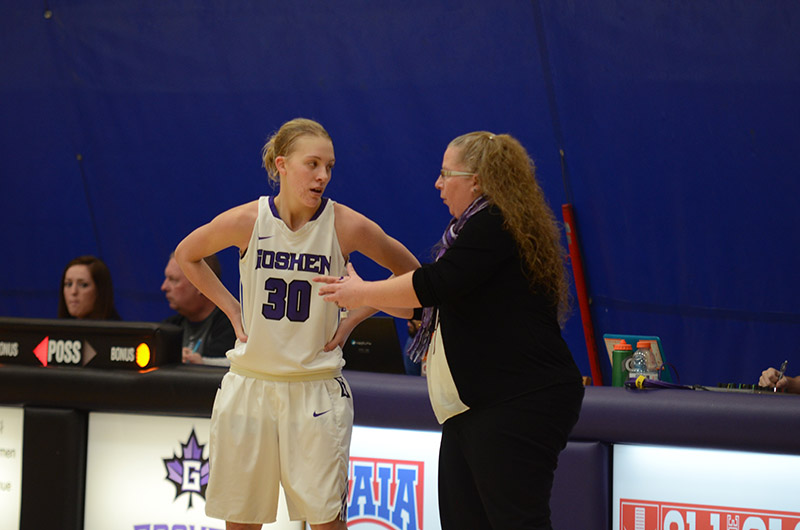 """Coach Stephanie Miller talks with a student on the women's basketball team during a game. The student is wearing a number """"30"""" Goshen jersey"""