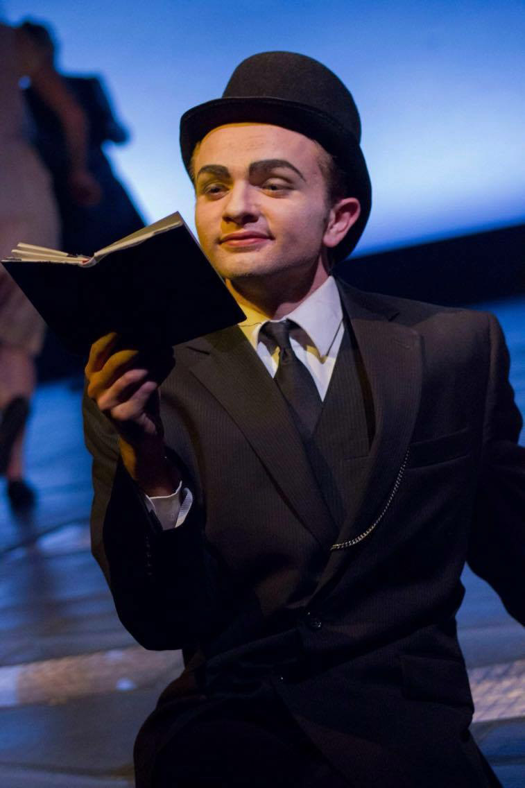 Martin Flowers performs in a production in Umble Center. He wears a black three piece suit and a bowler hat as he holds up a book that he is reading