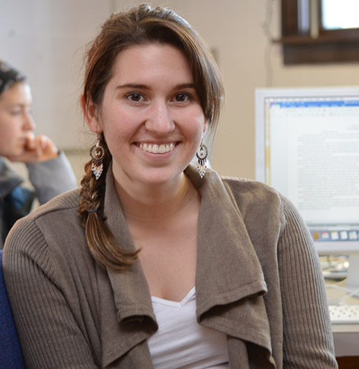Anna Cullar smiles for the camera; another student and a computer are in the background of the shot