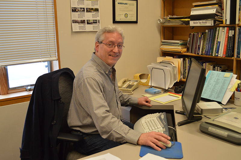 Jon Geiser sits at his desk and smiles for the camera, one hand on his mouse and the other resting on the desk