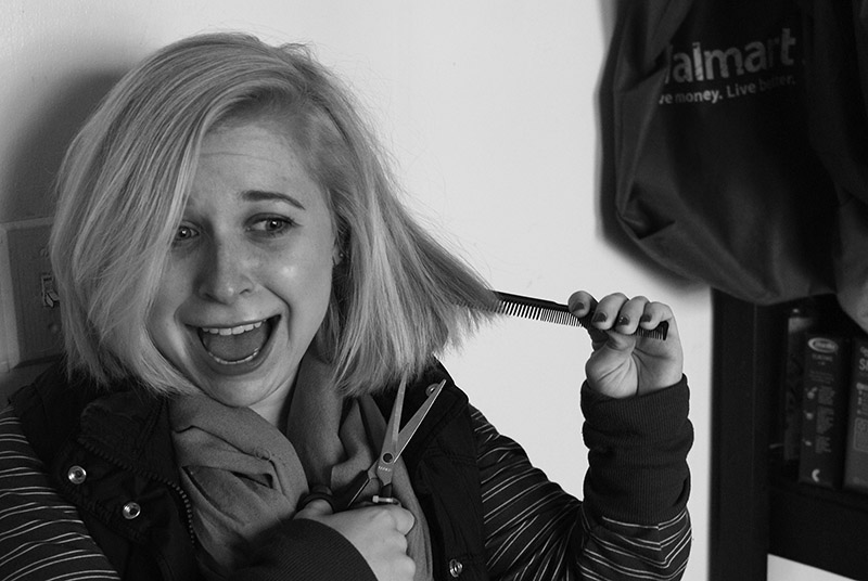 Black and white image of Halle Steingass preparing to cut her hair with scissors