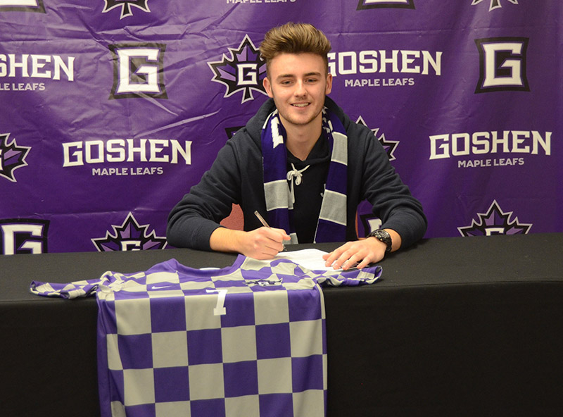 """Ollie Smith sits at a table in front of a purple """"Goshen Maple Leafs"""" backdrop and smiles as he signs a piece of paper. His purple and white checkered Goshen College jersey is on the table next to him."""