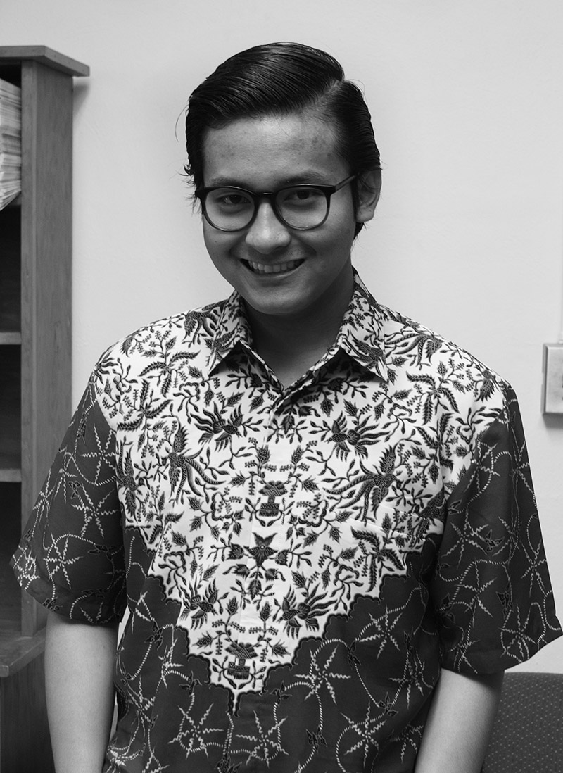 Black and white image of Galed Krisjayanta smiling for the camera in traditional Indonesian clothing