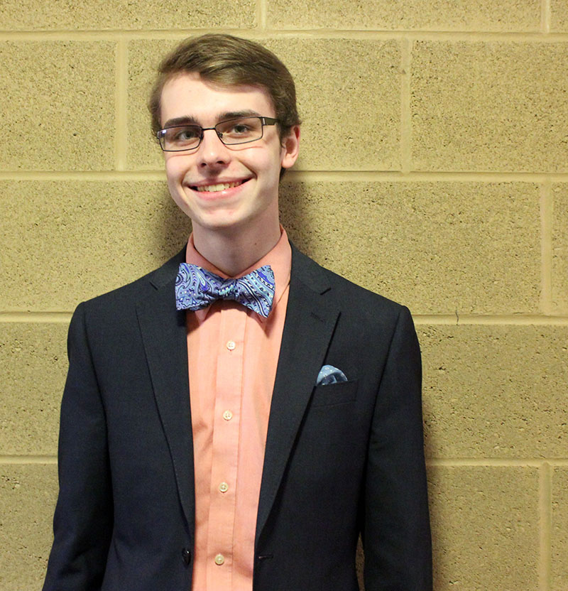 Lukas Thompson leans against a wall for a picture. He is wearing a black blazer, an orange button-up shirt, and a blue paisley bow tie
