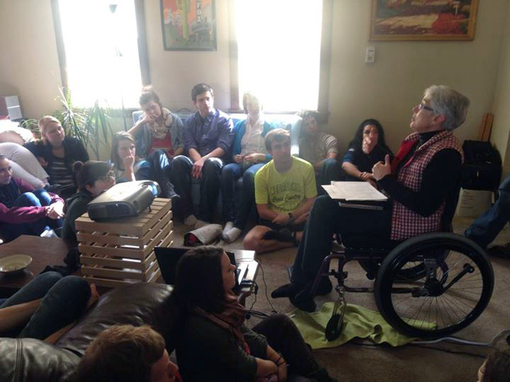 A large group of students crowds a dimly lit room in Prude House as Carolyn Shrock-Shenk addresses the group