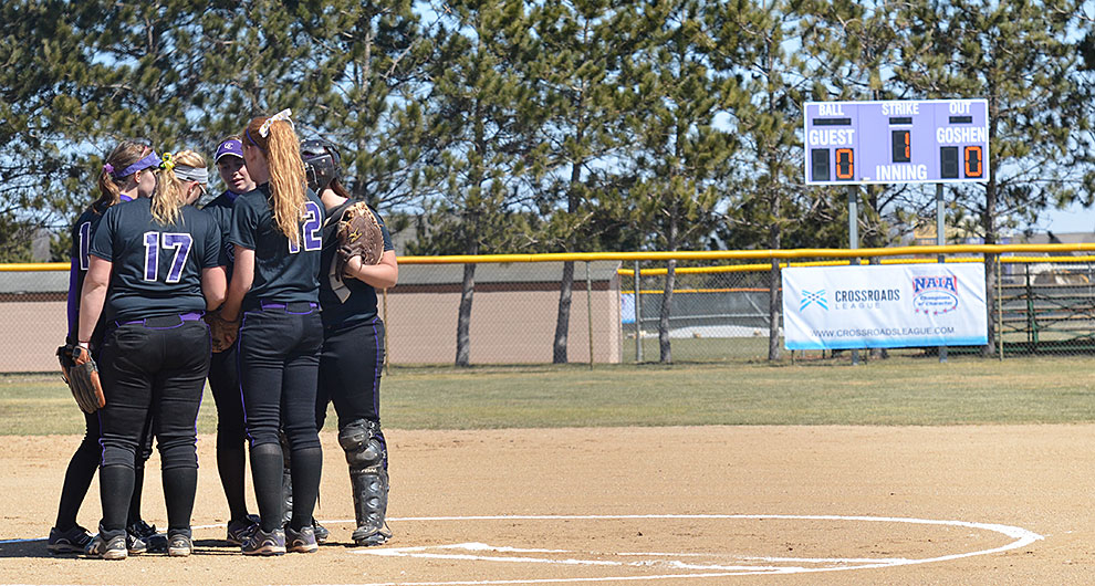 The Goshen softball team meets together in the pitcher's circle during a game