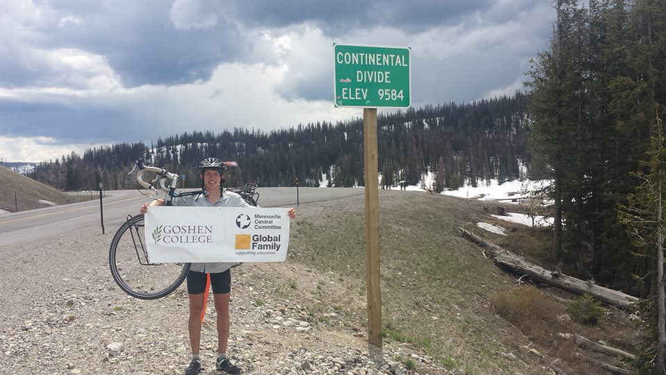 """Caleb Longenecker holds up a Goshen College advertisement card as he stands next to a """"Continental Divide: Elev. 9584"""" sign. A gravel road, mountains, and trees can be seen in the background. Caleb is wearing a bike helmet and is standing in front of his bike"""