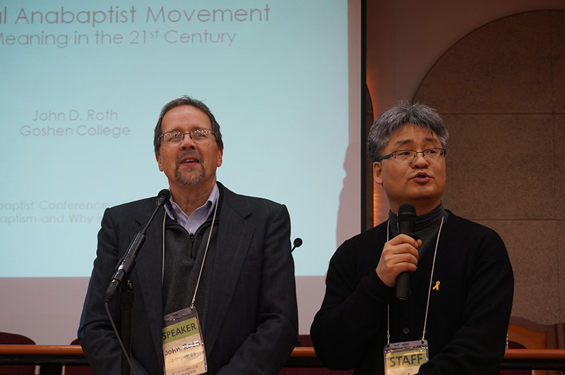 """John Roth and another man speak into microphones at a conference. The presentation behind them reads """"Anabaptist Movement... John Roth Goshen College"""""""