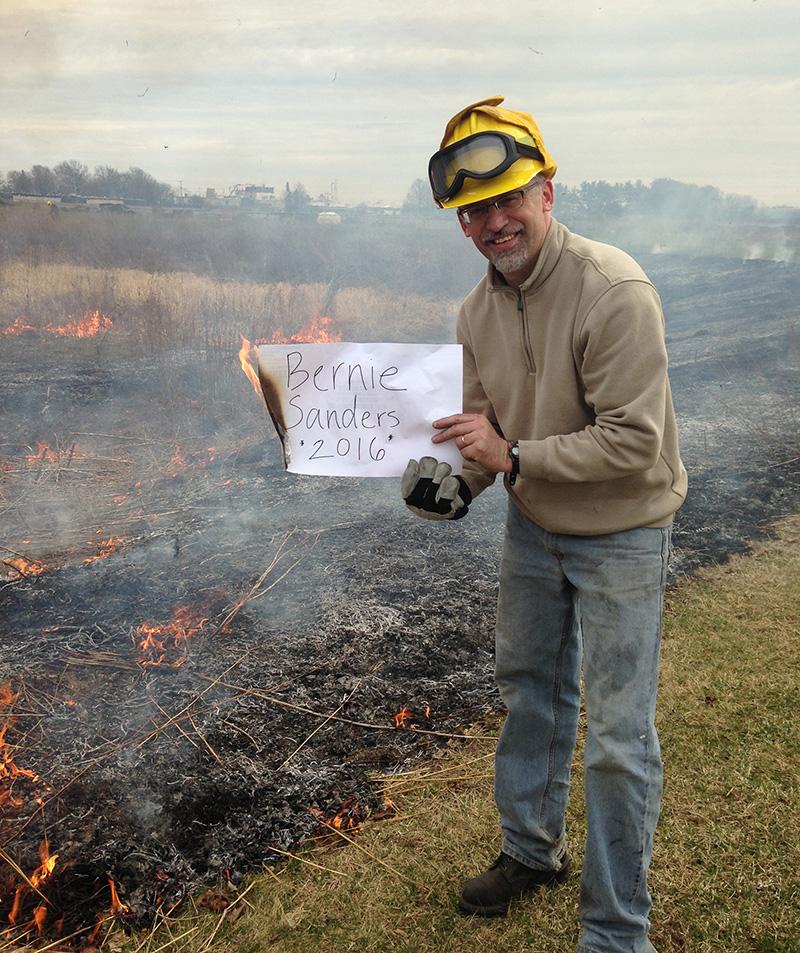 "Ryan Sensenig holds a ""Bernie Sanders 2016"" sign next to a burning prairie"