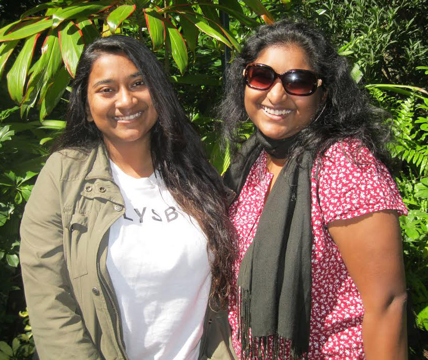 Prashansa Dickson and another woman smile for an outdoor picture, standing in front of a large-leafed plant