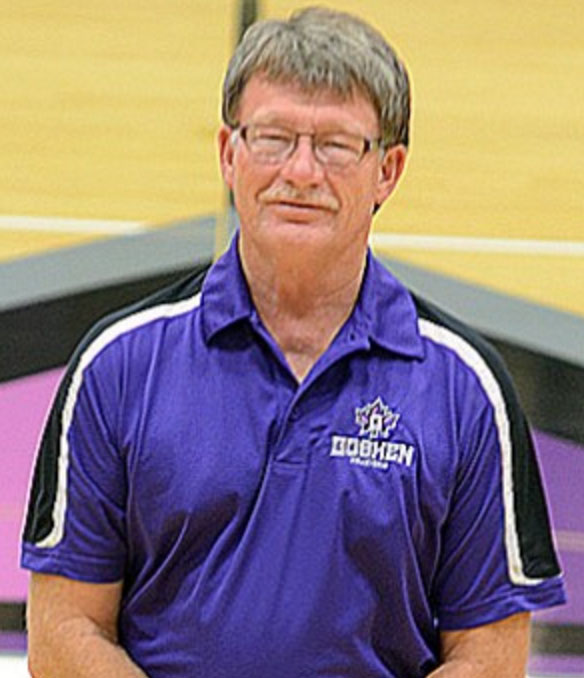 Headshot of Jim Routhier in the Goshen College gym. He is wearing a purple Goshen College shirt