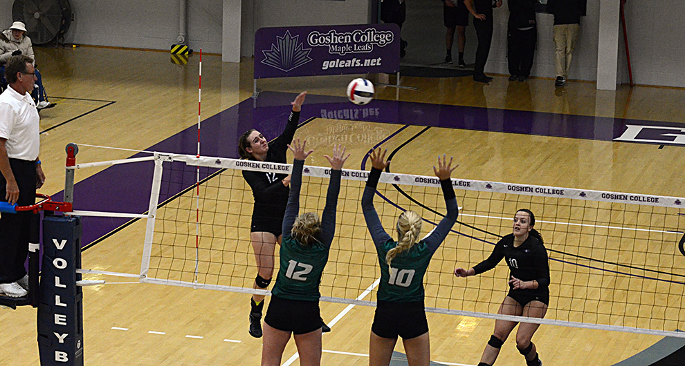 Katy Anspach and another member of the Goshen women's volleyball team jump to hit the volleyball over the net before two members of an opposing team