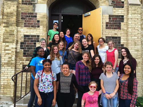 Alma Rosa Carillo Flores poses for a picture with a large group of adults and children who work with DOOR Chicago